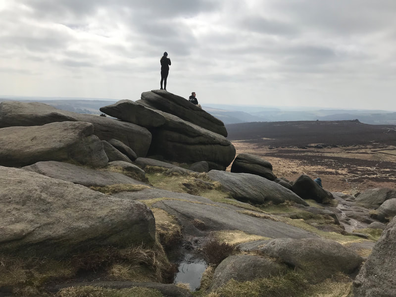 Visitors enjoying the view at Higger Tor on a Peak District scenic tour