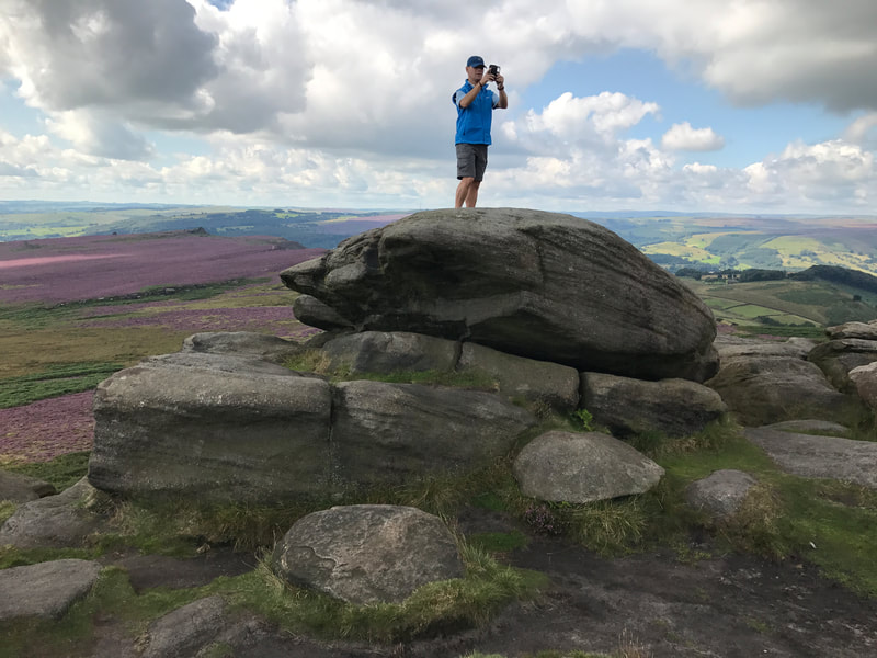 Photographer standing on gritstone boulders at Higger Tor