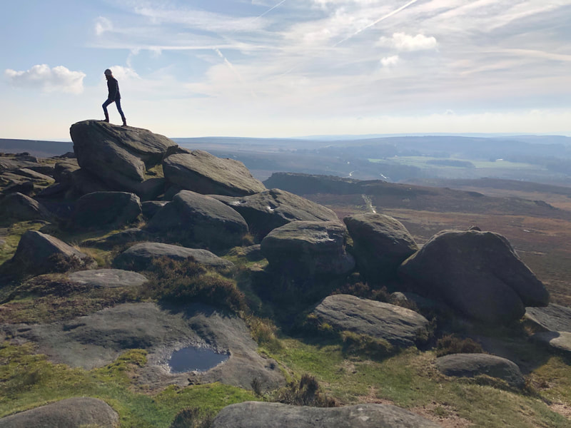 Climbing the rocks at Higger Tor in the Peak District